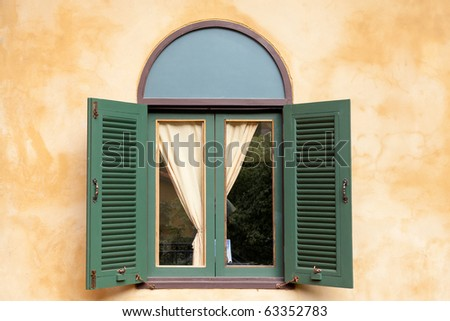 Italian window with yellow wall - stock photo