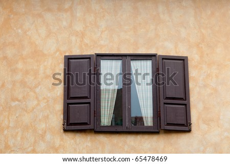 Italian windows opened on yellow wall