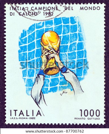 ITALY - CIRCA 1982: A stamp printed in Italy issued for Italy's World Cup Football Victory shows footballer holding aloft World Cup, circa 1982. - stock photo