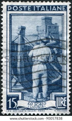 ITALY - CIRCA 1950: A stamp printed in Italy, shows Shipbuilding, in the background Rapallo Castle (Liguria), circa 1950 - stock photo