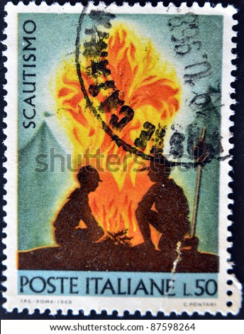 ITALY - CIRCA 1968: A stamp printed in Italy shows two boy scouts by the fire, circa 1968