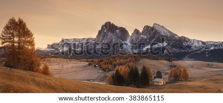 Italy. Dolomites. Autumn landscape with bright colors, house and larch trees in the soft sunlight. - stock photo