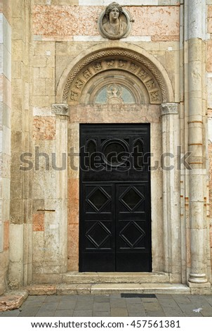Italy Ferrara old cathedral side door - stock photo