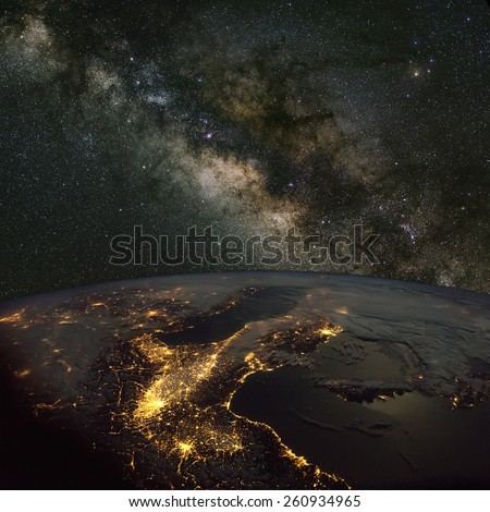 Italy from space at night with the Milky Way above. Elements of this image furnished by NASA.  - stock photo