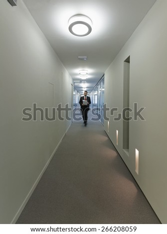Italy, man walking in a corporate building corridor - stock photo