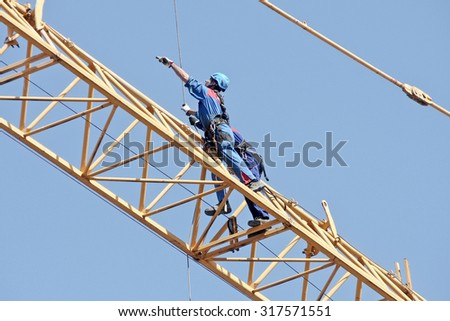 ITALY - MARCH 2014: Construction workers to work in a large urban yard. Dismantling of the crane.