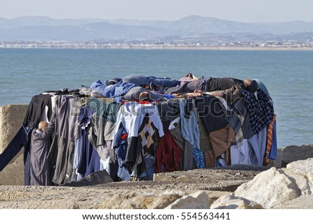 Italy, Mediterranean Sea, Sicily, Scoglitti (Ragusa Province); 8 March 2011, african immigrants sleeping on a concrete block in the port, while their clothes are drying under the sun - EDITORIAL