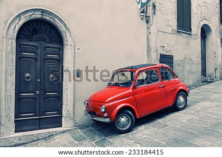 ITALY, MONTEPULCHANO - MAY 16, 2014: Old red Fiat 500 R to stand near a wall. Fiat Nuova 500 (ital. cinquecento) - the car made by the Fiat company with 1957 on 1975 - stock photo