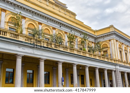 Italy, Novara. Yellow building with columns and green plants - stock photo