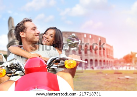 Italy Rome couple on scooter by Colosseum. Romantic happy lovers driving scooter on honeymoon having fun in front of Coliseum. Love and travel concept with multiracial couple.