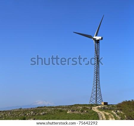 ITALY, Sicily, Catania province, countryside, Eolic energy turbines (volcano Etna in the background) - stock photo