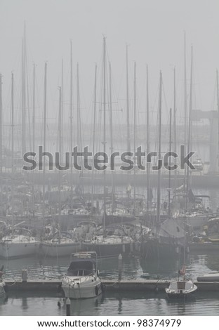 Italy, Sicily, Mediterranean sea, Marina di Ragusa, view of luxury yachts in the marina in a foggy day - stock photo