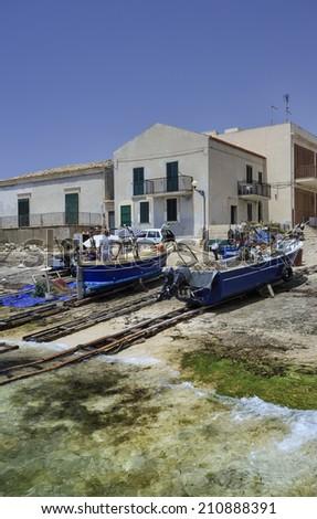 Italy, Sicily, Mediterranean sea, Sampieri (Ragusa Province), fisherman working ashore on his fishing boat - stock photo