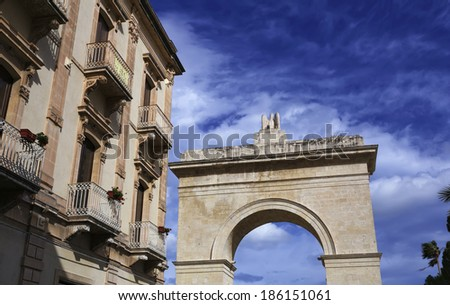 Italy, Sicily, Noto (Siracusa Province), baroque building and the Porta Reale stone Arc - stock photo