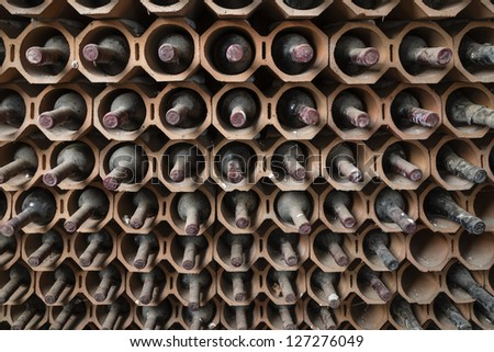 Italy, Sicily, old red wine bottles aging in a wine cellar - stock photo