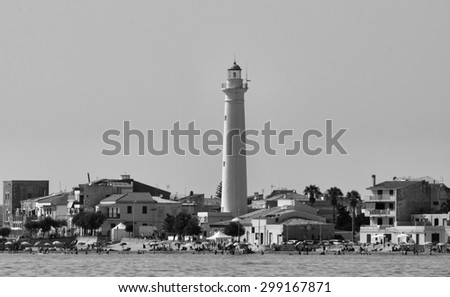 ITALY, Sicily, Punta Secca (Ragusa Province), lighthouse and people on the beach - stock photo