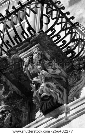 Italy, Sicily, Ragusa Ibla, the baroque facade of Cosentini Palace (Unesco monument), ornamental statues under a balcony - stock photo
