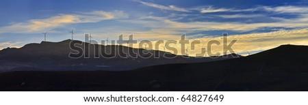 ITALY, Sicily, Sicani mounts, Eolic energy turbines at sunset - stock photo