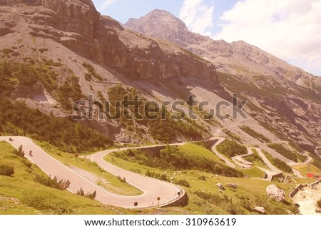 Italy, Stelvio National Park. Famous road to Stelvio Pass in Ortler Alps. Alpine landscape. Retro filtered color style. - stock photo