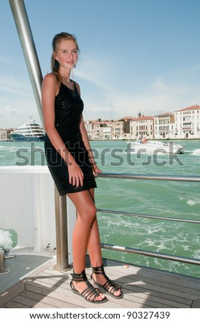 Italy, travel by yacht to Venice - beautiful young girl on the yacht, in background Venetian lagoon