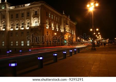 Italy, Trieste, piazza Unità d'Italia traffic passing by night - stock photo