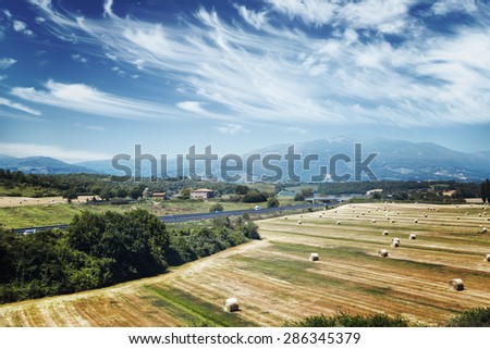 Italy. Tuscany. Rural landscape with view of farm fields and mountains - stock photo