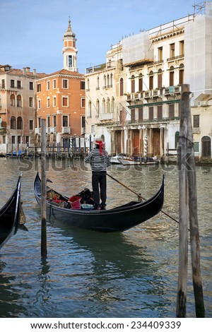 ITALY, VENICE - November 20: Gondolier on a gondola on the Grand Canal on November 20, 2014 in Venice. Gondola's are a major mode of touristic transport in Venice, Italy.
