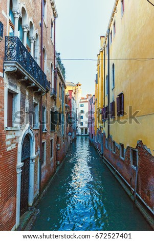Italy; Venice, 02/25/2017. Street with colored walls of houses and reflection in the water.