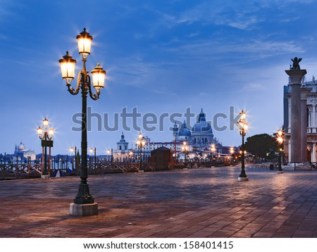 Italy Venice sunrise view on st marco square and Sana Maria Della Salute cathedral between illuminated street lamps