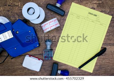Item inventory stock list card, black pen, stamp pad and price tagging gun over wooden background flat lay - stock photo