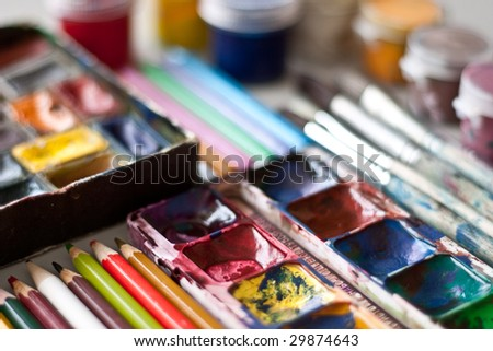Items for drawing and art: watercolor paint, brushes, colored pencils. - stock photo