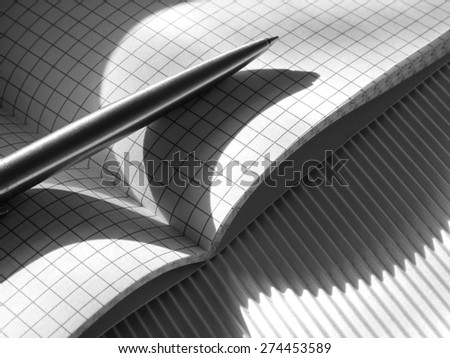 Items for writing - pen, squared notebook disclosed in a cage, illuminated by solar rays, the shadow of unusual shape. Black and White - stock photo