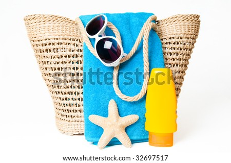 Items ready for a day at the beach with towel, suntan lotion and sunglasses - stock photo
