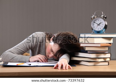 Its late for young student girl who falls asleep doing her homework. - stock photo