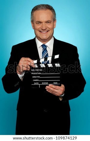 Its showtime. Businessman holding clapperboard - stock photo