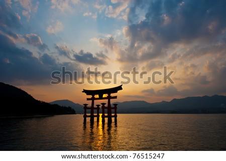 Itsukushima Shrine with Miyajima Torii silhouette at dusk. - stock photo