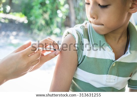 ittle boy looking at his arm, while receiving vaccine - stock photo