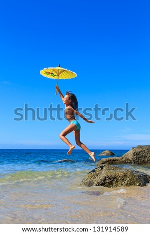 ittle girl on a beautiful day at the beach holding a yellow umbrella and jumping off the rocks - stock photo