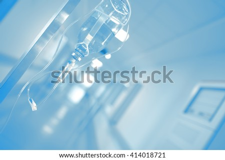 Iv drip in blurred hospital hallway. - stock photo