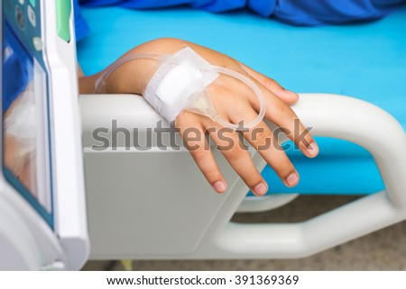 iv drip in child patient's hand - stock photo