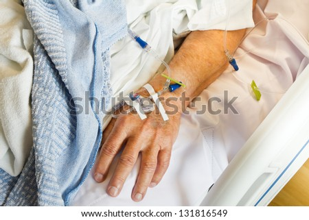 IV in hand of patient lying in hospital room bed close up - stock photo