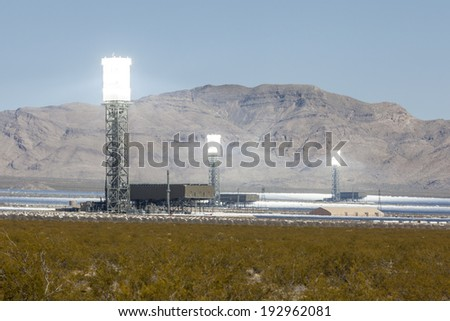 IVANPAH, CALIFORNIA - May 14, 2014:  Three glowing white hot towers at the newly operational 392 megawatt Ivanpah solar thermal power plant in California's Mojave desert.    - stock photo