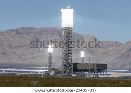 IVANPAH, CALIFORNIA - November 26, 2014:  Focused mirrors producing intense heat shimmers at the massive 392 megawatt Ivanpah solar power plant in California's Mojave desert.   - stock photo