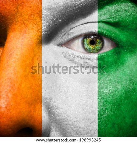 Ivory Coast flag painted on a man's face to show support for Ivory Coast - stock photo