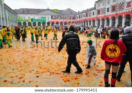 IVREA - MARCH 3: Carnival of Ivrea. The battle of oranges. By the end of the day, the squares of Ivrea with the juice of oranges.  On March 3, 2014 Ivrea, Italy. - stock photo