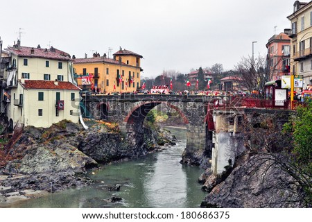 IVREA - MARCH 3: Carnival of Ivrea. The battle of oranges. The throwing on a bridge of Ivrea town. On March 3, 2014 Ivrea, Italy. - stock photo