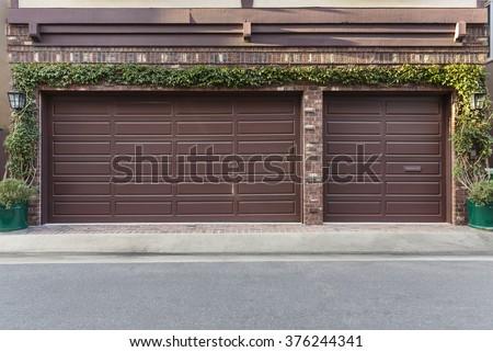 ivy on the wall of three car garage doors - stock photo