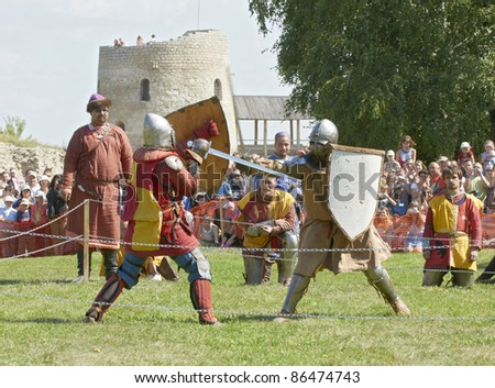 "IZBORSK, RUSSIA - AUGUST 6: Unidentified men in knightly armor take part in festival ""Iron hailstones"" on August, 6 2011 in Izborsk, the Pskov area, Russia. - stock photo"