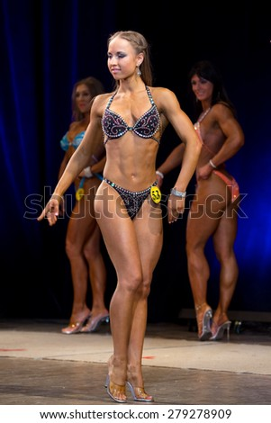 Izhevsk, Russia - April 18, 2015. Open championship of the Volga Federal District of bodybuilding and fitness bikini. The brunette in a gray bikini stands sideways - stock photo