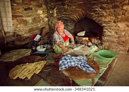 IZMIR PROVINCE, TURKEY - AUG 2: Elderly woman cooking traditional Gozleme dish in rustic stone oven of old turkish village on August 2, 2015. Population of Izmir province is 3.950.000 people - stock photo